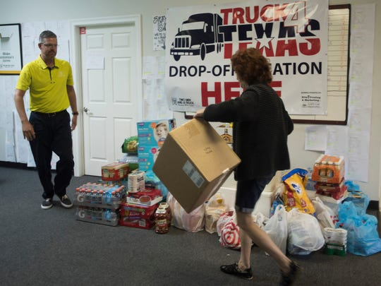 Two Men and a Truck owner, Greg Micklos, left accepts supplies for the recovery effort in Texas from Pensacola resident, Kathi Gordon, right,  Wednesday morning Aug. 30, 2017.