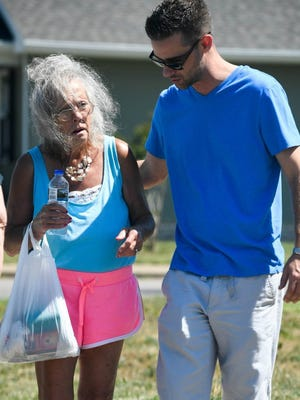 Chris Metz, assistant director at Echo House, helps 67-year-old Cynthia Phelps to the Aurora Homeless Outreach van after they found a bed for the woman at a local shelter Friday. Phelps lost her apartment two years ago and has been bouncing around on and off the streets ever since.