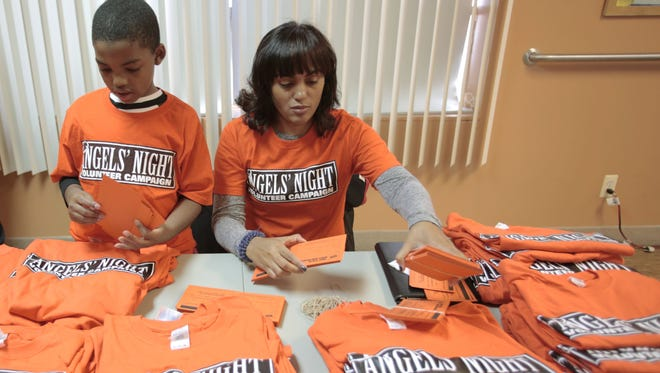 Cherie Polk, right, and her son Jordan, 7, organize commitment slips at the Life Builders building on Saturday, Oct. 11, 2014 in Detroit. Volunteers along with Mayor Mike Duggan went door to door in the neighborhood to recruit neighbors to watch out for their areas on Angels' Night.