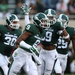 Michigan State players celebrate after a tackle Aug. 29, 2014.