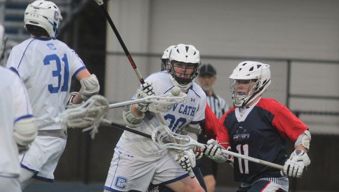Jacob Shriver of CovCath, left, and JT Lokey of the NKY Warriors look for an opening during the Northern Kentucky Warriors' 12-11 win over Covington Catholic in lacrosse March 28, 2018 at Covington Catholic, Park Hills KY.