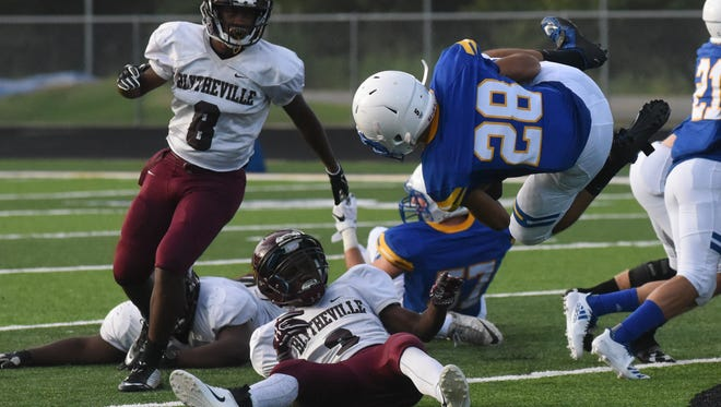 Mountain Home running back Reese Wendfeldt spins in the air after colliding with a Blytheville defender.