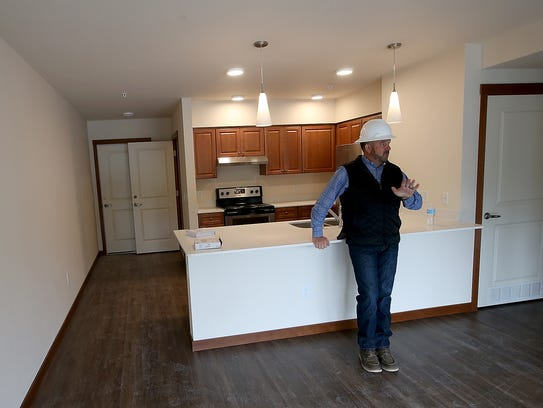 Kelly Clark, president of Chinook Contractors, gives a tour of one of the units at the Arendal on Viking apartment complex in Poulsbo.