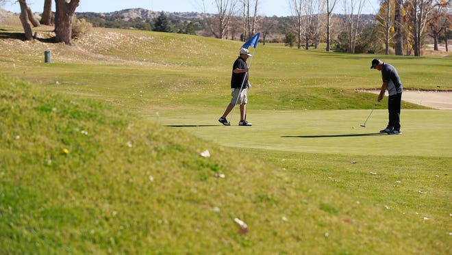 A pair plays golf on Nov. 11 at the Aztec Municipal Golf Course.