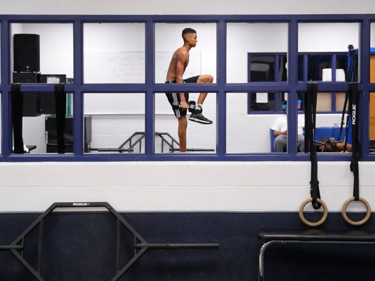 In this Oct. 10, 2017, photo, Emoni Bates works out in a weight room in Ypsilanti, Mich. The coveted young basketball player is a low-key honor roll student. (AP Photo/Paul Sancya)