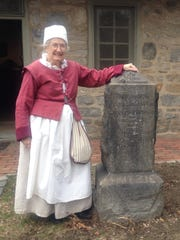 Longtime New Sweden Centre member Alesa Hogate, shown in colonial-style attire by a monument she worked to get moved to the Old Swedes Historic Site in Wilmington, says the nonprofit program sponsoring Saturday's seminar welcomes new members of all ages, with special programs for students.