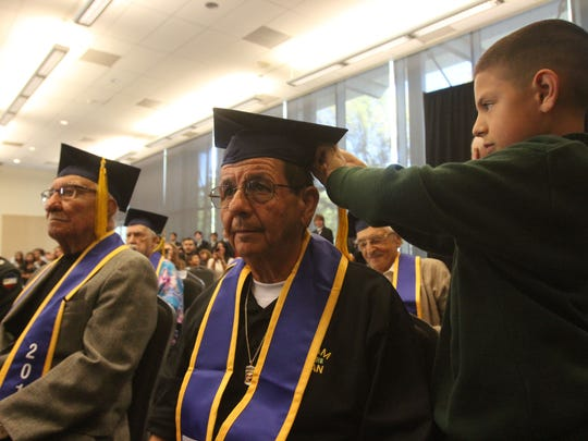 Grandson David Peña Jr., fixes Juan Peña's tassel during the 9th annual Operation Recognition Ceremony for veterans. Peña, who served in the Marine Corps, received a high school diploma at the Moreno Valley Conference and Recreation Center in Moreno Valley on November 10, 2015.