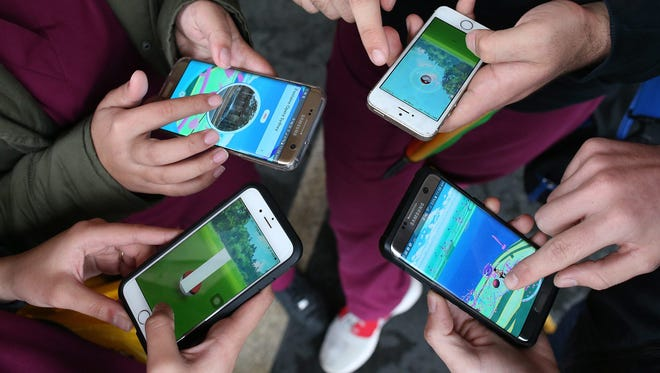 People play Pokemon Go on their mobile phones.