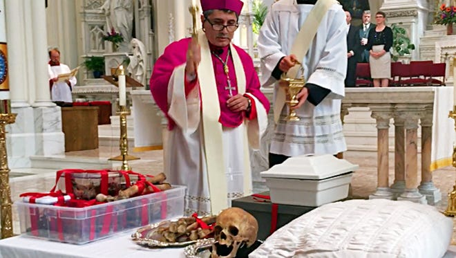 Auxiliary Bishop Jorge H. Rodriguez-Novelo blesses the remains of Julia Greeley in the Cathedral Basilica of the Immaculate Conception in Denver on Wednesday, June 7, 2017. The former slave known for charity work is being studied for possible sainthood. Her remains were exhumed from a suburban cemetery and placed in a wooden box for veneration during the ceremony. (AP Photo/Colleen Slevin)