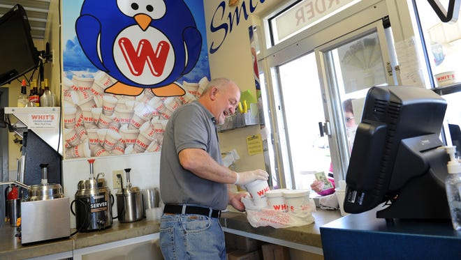 Co-owner Terry Wells prepares an order for a customer at Whit's Frozen Custard on Maple Avenue in Zanesville.