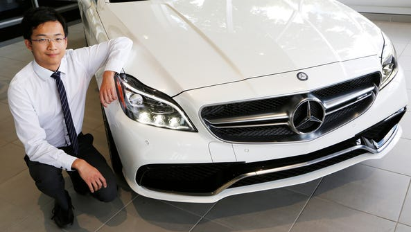 Professional Sales Associate Yuchen Zhang with a Mercedes