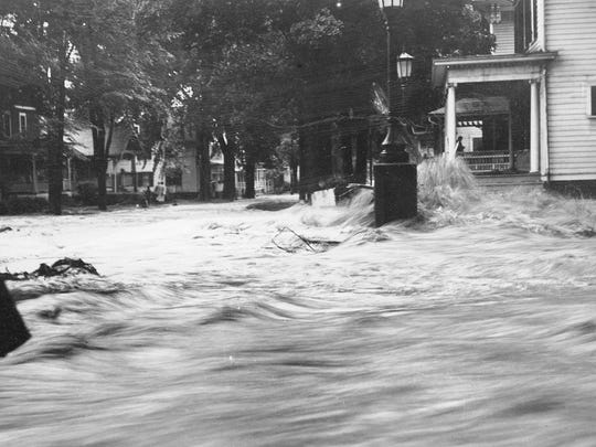 A torrent of flood water forms a rapid off a porch on North Aurora Street during Ithaca's devastating flood in July 1935. The storm is estimated to have killed more than 100 people throughout New York state and caused $1.5 million of damage in Ithaca.