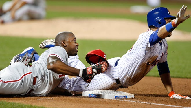 Philadelphia Phillies' first baseman Ryan Howard, left, tags New York Mets' James Loney out on a sixth-inning groundout that struck Phillies' relief pitcher Luis Garcia on the leg.