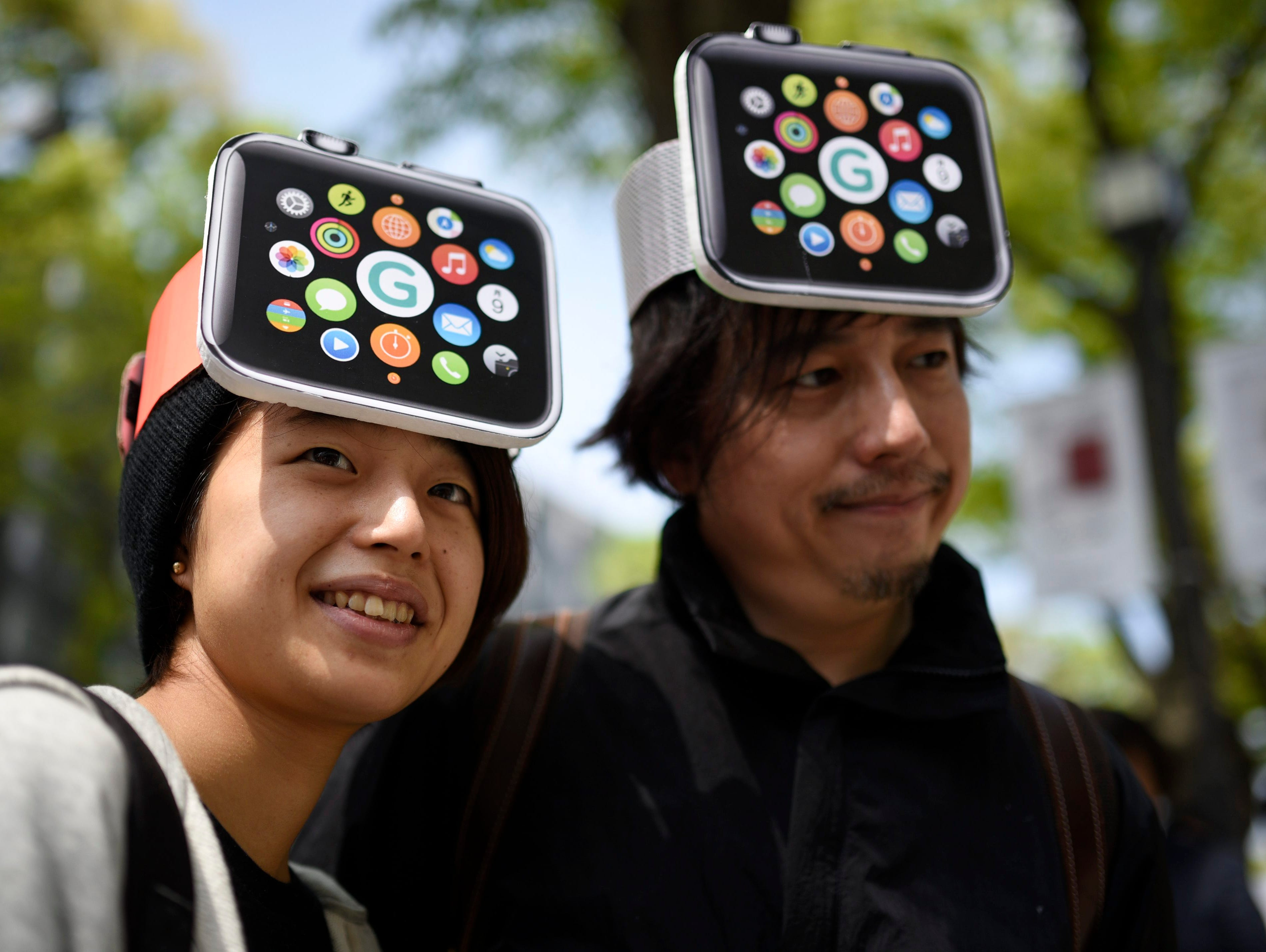 Apple products fans Makoto Saito, left, and her friend Kazumi Oda, wait to enter a Japanese telecommunication store to purchase the Apple Watch in Tokyo.