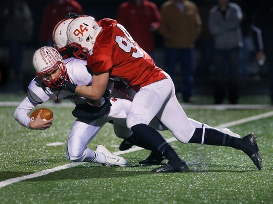 Center Grove defenders Gavin Everett, No. 94, and Jovan