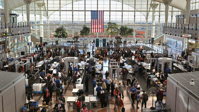 Passengers move through a main security checkpoint at the Denver International Airport.