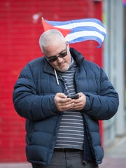 A man on his phone and carrying a Cuban flag along Bergenline Avenue in North Bergen on Saturday.