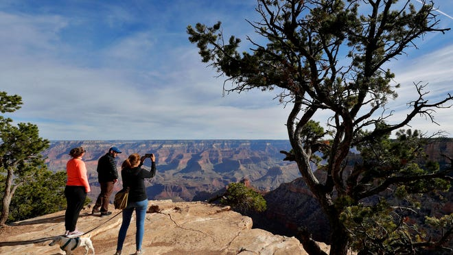 Tourists gather for a view of the Grand Canyon in Arizona. Grand Canyon National Park officials tentatively plan to reopen the park's eastern entrance in late May, but there's sentiment in Page, Ariz., a tourist-dependent small city where many campsites and other facilities remain empty, that sooner would be better.