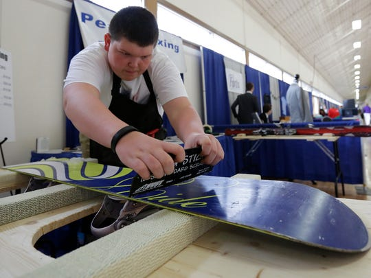 Peak Waxing owner Lukas Lindner waxes a snowboard as a demonstration during Thursday's Small Business Expo event at Central Wisconsin Convention & Expo Center in Rothschild.