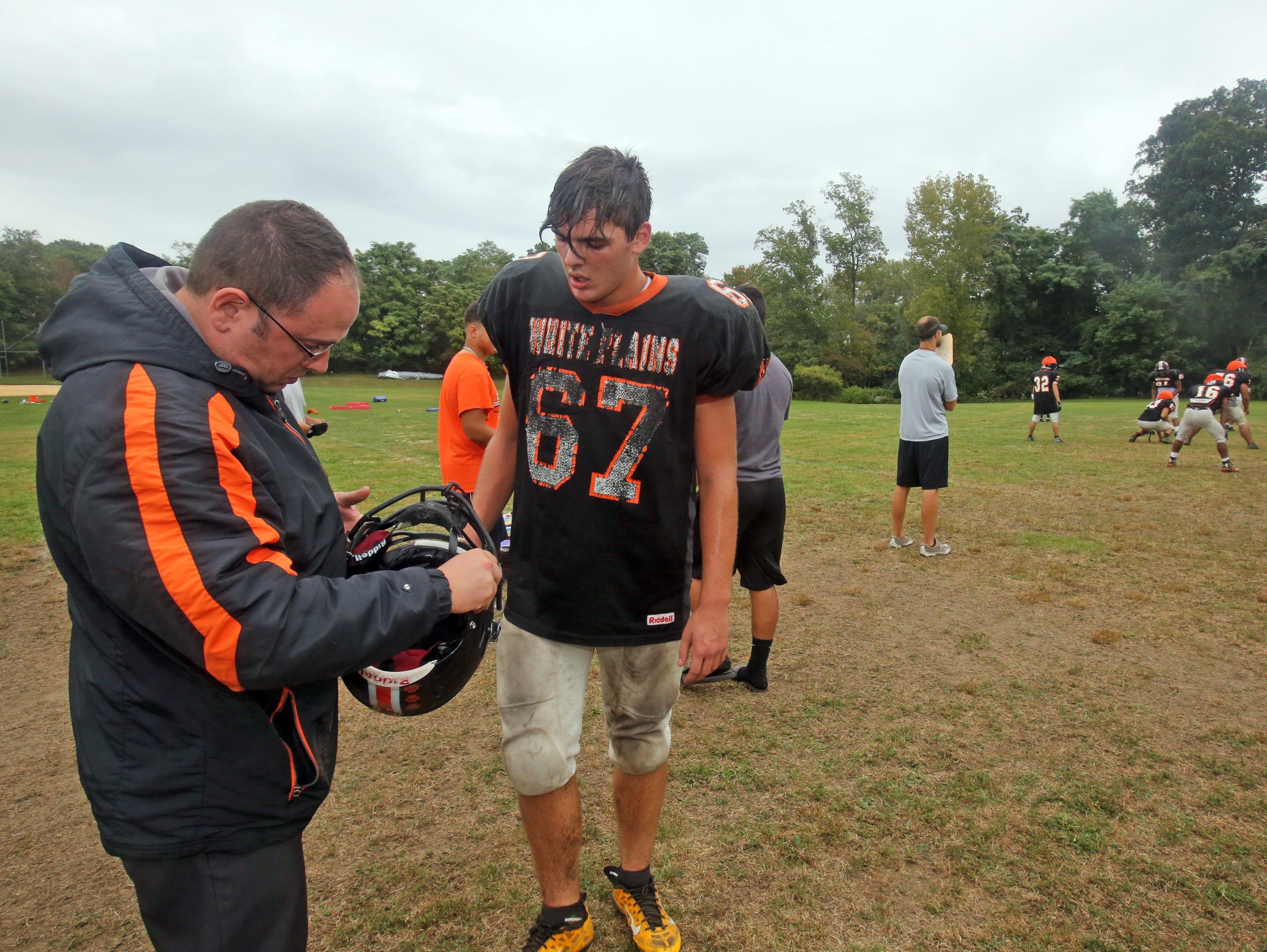 Mike Mirabella, the athletic trainer at White Plains High School, repairs Ernik Docaj's helmet during varsity football practice Sept. 29, 2015.