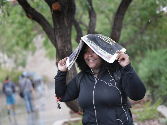 University of Texas at El Paso student Courtney Henderson uses a copy of the student newspaper, The Prospector, to shield herself from the rain between classes Tuesday on campus.