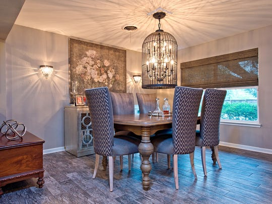 The formal dining space's bird cage chandelier and crystal sconces give great light and shadows to the space