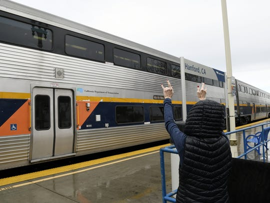 A woman waves goodbye to passengers leaving Hanford on the Amtrak train headed to Jack London Square in Oakland Wednesday morning.