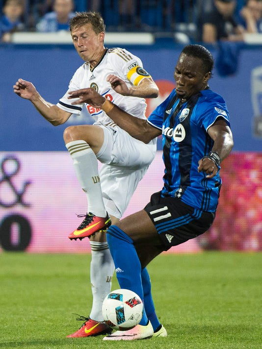 Montreal Impact's Didier Drogba, right challenges Philadelphia Union's Brian Carroll during the second half of an MLS soccer match in Montreal on Saturday, July 23, 2016. (Graham Hughes/The Canadian Press via AP)