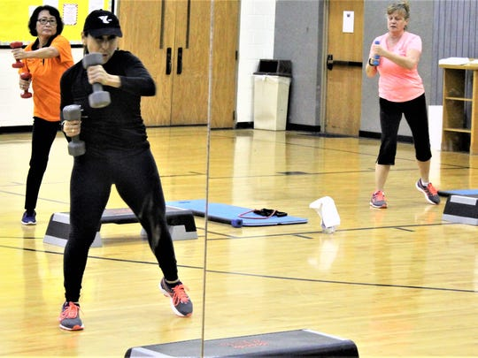 "A mirror reflects instructor Ruby Hoffman and two participants in a Thursday afternoon ""Tone Up"" class at the Redbud YMCA."