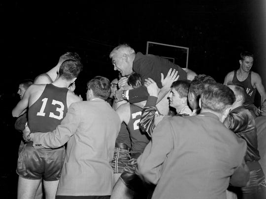 Indiana coach Branch McCracken is carried off the floor by the Hoosiers after they defeated Kansas in the NCAA finals in Kansas City, Missouri, March 18, 1953.