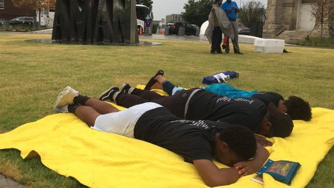 Teenagers lie prostrate in worship during a light rain during the Keeping It Real Bible Study on The Road event on Wednesday, June 20, 2018 at the I Am a Man Plaza next to Clayborn Temple in Downtown. From left, the teenagers are Tony Sims, 18, Miles Thomas, 17, and Alexandria Faulkner, 17.