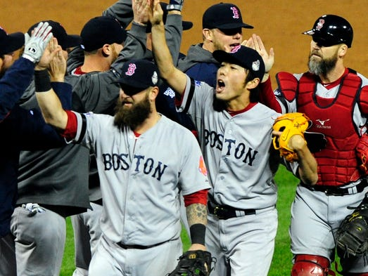 Red Sox players celebrate after defeating the St. Louis Cardinals at Busch Stadium.
