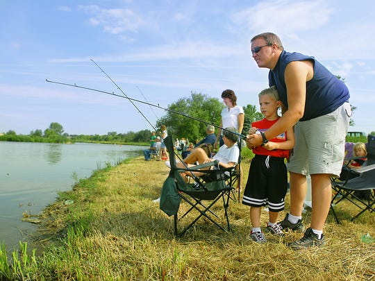 Mike Polich of Two Rivers helps his son Isaiah detect a bite on his fishing rod as they participate in the kids fishing derby at the 27th street boat ramp in Two Rivers. The event was part of the Two Rivers Kiwanis Fish Derby and Festival in 2016.