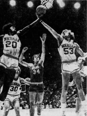 Three arms are extended towards the ball during the Indiana-Michigan basketball game, Jan. 10, 1976.