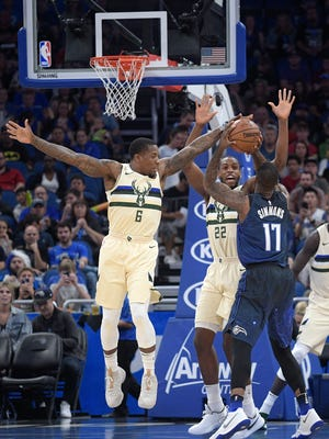 The Bucks' Eric Bledsoe (6) and  Khris Middleton  defend a shot by Orlando Magic forward Jonathon Simmons in a recent game.
