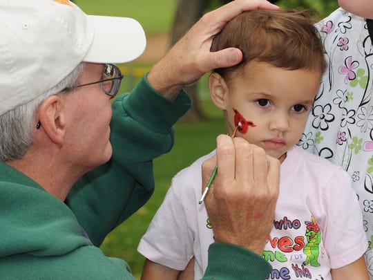 Brenya Sovay,  right, 2, daughter of Tiffany Savay, of Whiteland, gets a little red pig painted on her face by Steve Warner of the Southside Art League at the inaugural WAMMfest held in Craig Park in Greenwood, IN, Saturday August 22, 2009. The festival featured local food, wine, art, music and beer. Phil Meyers/For The Star