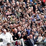 Pope Francis greets faithful as he leaves at the end of the Palm Sunday Mass in St. Peter's square at the Vatican, Sunday, April 13, 2014. Tens of thousands of Romans, tourists and pilgrims have joined Pope Francis in a solemn Palm Sunday service in St. Peter's Square. Palm Sunday begins Holy Week, which culminates next Sunday on Easter. Francis used a pastoral staff made of wood carved by Italian prison inmates, who donated it to him. The pope is determined to put people on the margins of life at the center of the Roman Catholic church's attention.