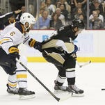 The Sabres' Mike Weber grabs the jersey of the Penguins' Chris Kunitz, resulting in Kunitz being awarded a penalty shot on Saturday.