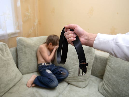 A man holding a black belt in front of a crying child