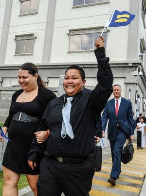 Loretta Pangelinan, front right, proudly raises a miniature equal rights flag into the air as she and her partner, Kathleen Aguero, exits the U.S. District Court of Guam building in Anigua on June 5. The couple filed a lawsuit in April after they were denied the application for a marriage license at the Department of Public Health and Social Services. On June 5, the same sex couple won a ruling handed down by a federal judge, that declares a Guam law, that defines marriage as a union between couples of the opposite sex, to be unconstitutional.