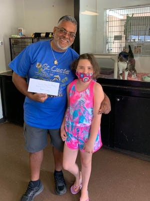 Ralph Gonzalez, director of the Humane Society of Port Jervis/Deerpark, accepts a $500 donation from Ella Sandberg, 8.