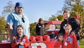 Alumni with small children celebrate Rutgers Homecoming in style on the lawn of the president's home at R Family Fall Festival.