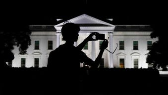 FILE - In this Aug. 25, 2017, file photo, a tourist takes a photo from Pennsylvania Avenue of the illuminated White House in Washington. The White House is embarking on a major campaign to turn public opinion against the nation's largely family-based immigration system ahead of an all-out push next year to move toward a more merit-based structure.