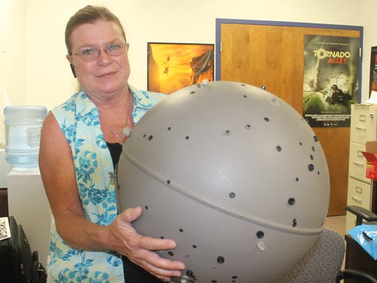 Marketing and Public Relations Director Cathy Harper holds the star projector from the museum's old planetarium system.