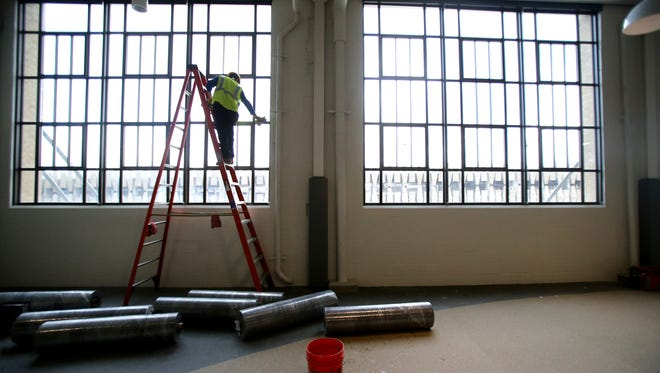 Solomon Lopez whips down windows in a group exercise area of the Church Health YMCA at Crosstown Concourse.