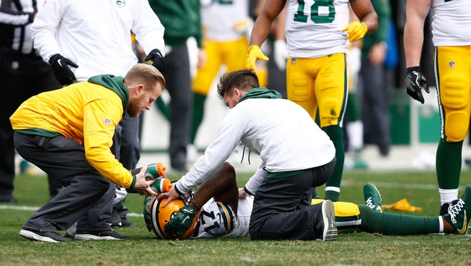 Green Bay Packers wide receiver Davante Adams gets medical attention after a hit in the third quarter of Sunday's game against the Carolina Panthers at Bank of America Stadium.