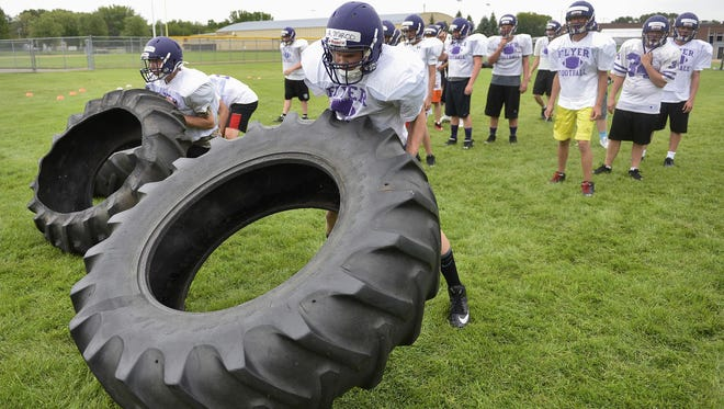 Little Falls football players roll tractor tires as a strength drill during practice Aug. 13 at the school.