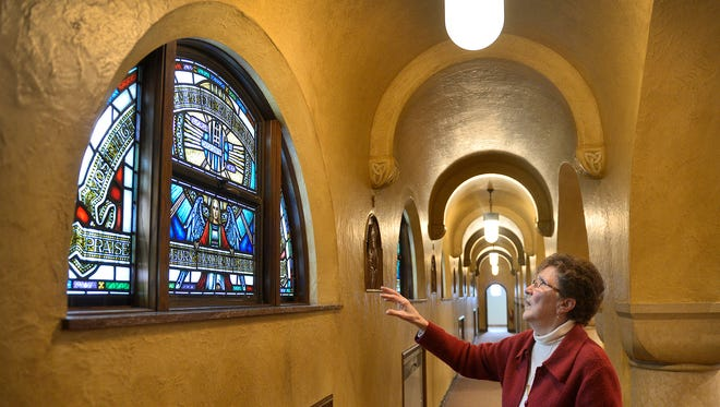 Franciscan Sister Bea Eichten talks about the architecture and stained glass inside one of the cloister walks at the sisters' Sacred Heart Chapel Thursday, Feb. 11, in Little Falls. The windows depict the verses of the Canticle of the Sun. The sisters are celebrating their 125th year in Little Falls.