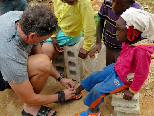 In this 2014 photo, Brian Nettle assists a Haitian