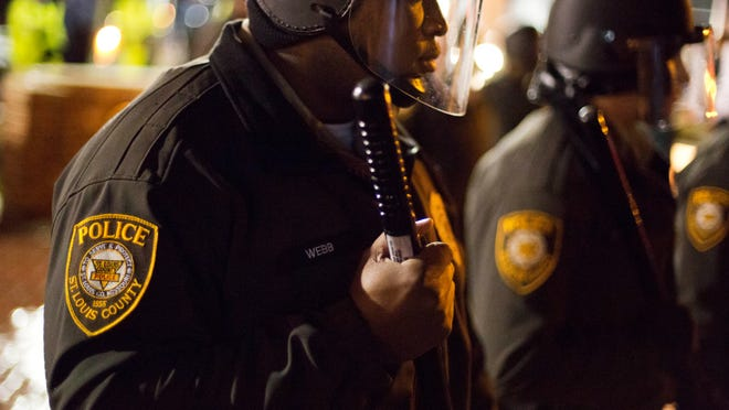 Police stand guard during a demonstration outside the Ferguson Police Department, Saturday, Nov. 22, 2014, in Ferguson, Mo. Ferguson and the St. Louis region are on edge in anticipation of the announcement by a grand jury whether to criminally charge Officer Darren Wilson in the killing of 18-year-old Michael Brown. (AP Photo/David Goldman)